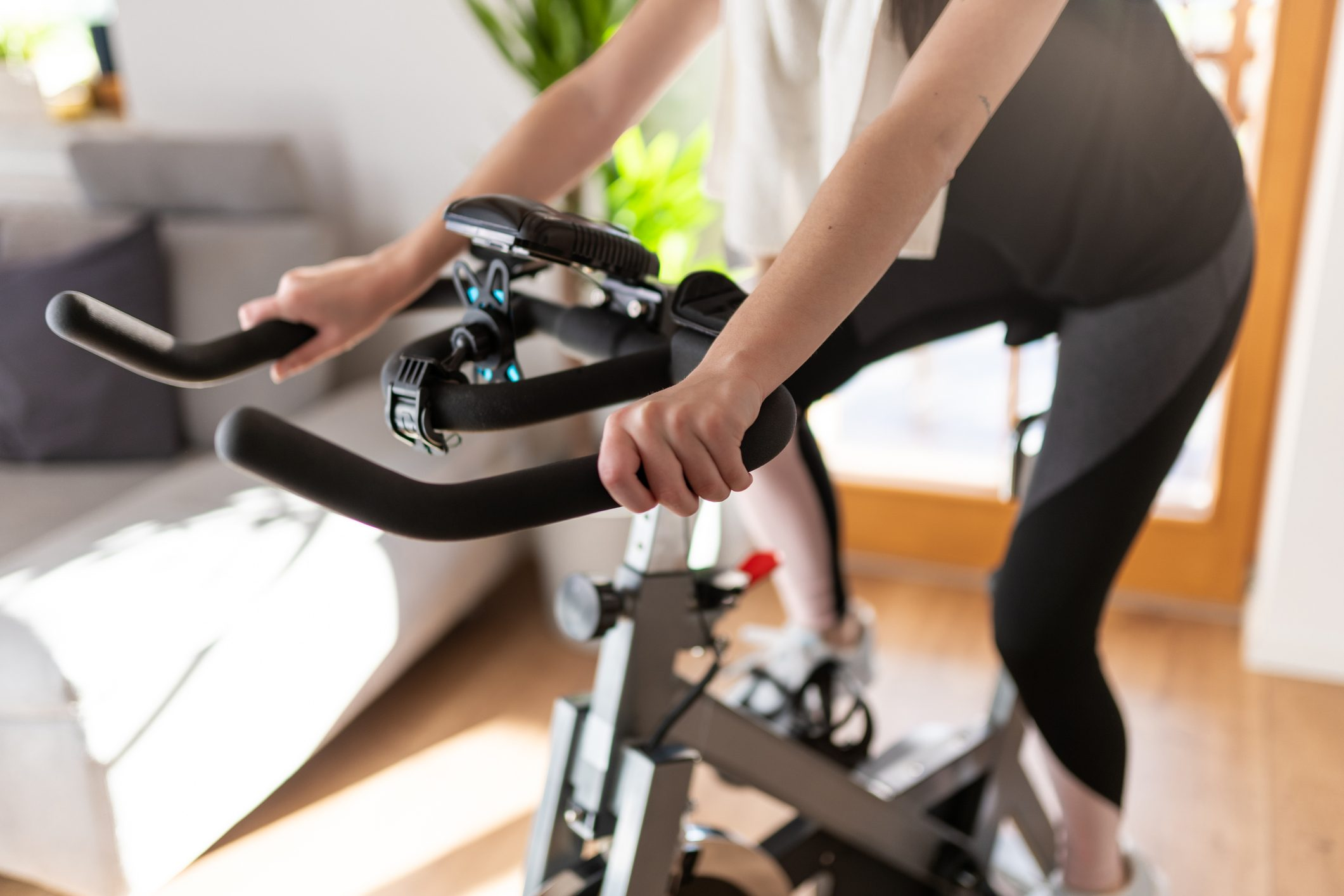 Low section of woman training on exercise bike at home