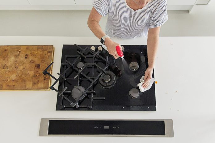 Overhead view of a woman cleaning her gas hob