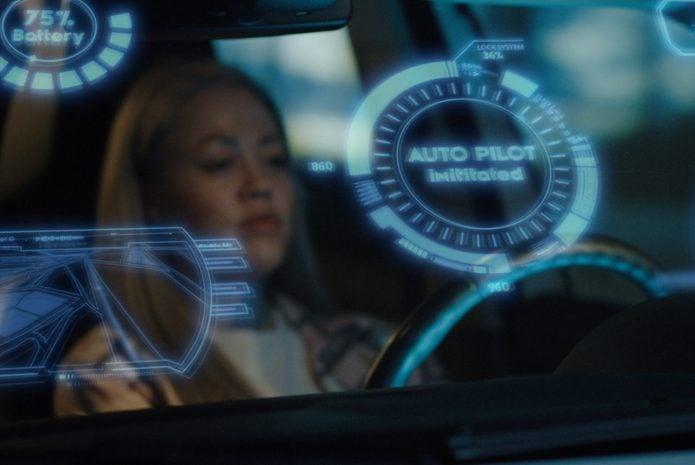 Woman engaging self driving mode in car