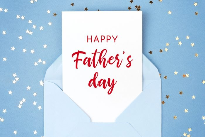 Happy Father's day greeting card in blue envelope on blue background decorated with confetti.