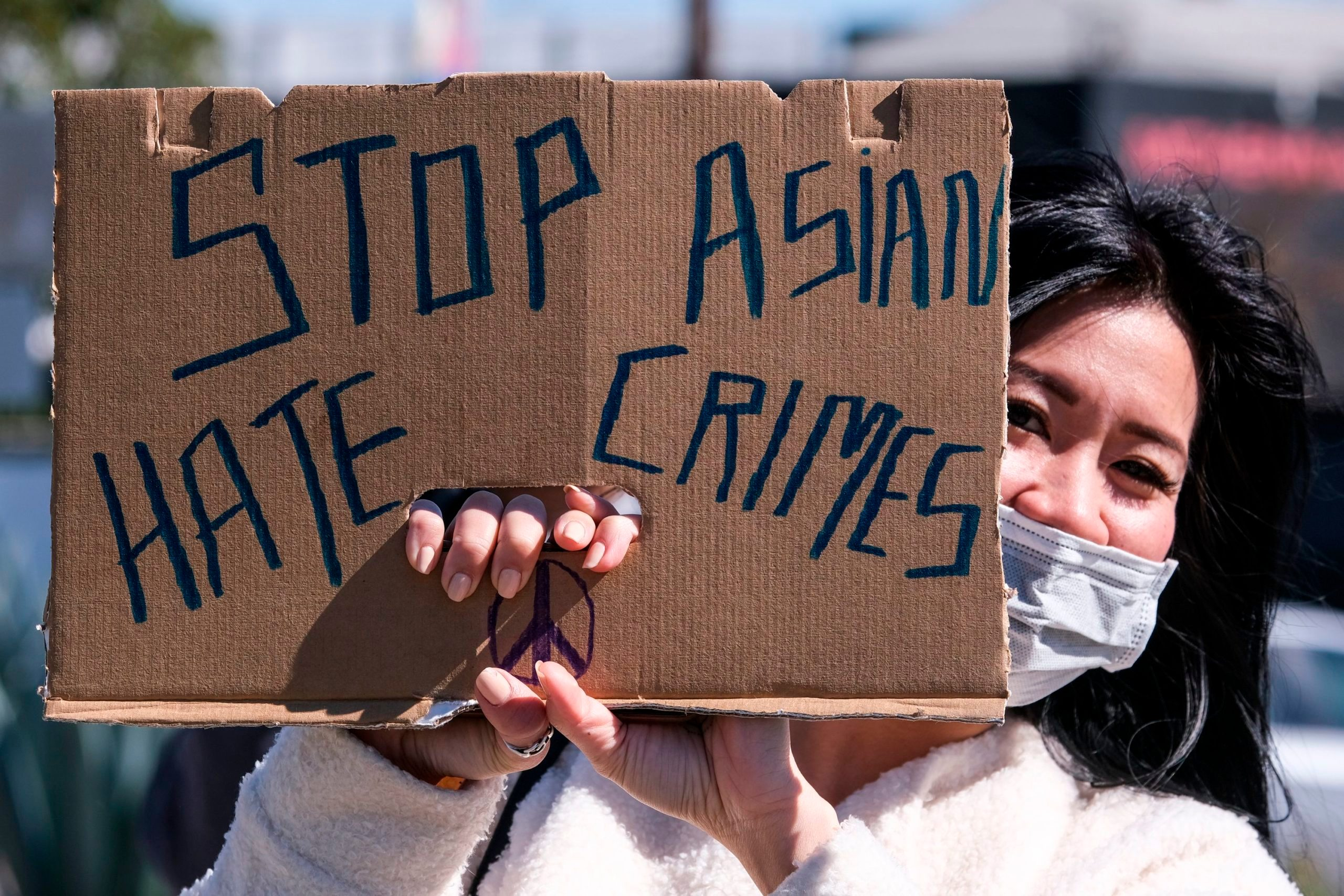 A demonstrator wearing a face mask and holding a sign takes part in a rally to raise awareness of anti-Asian violence, near Chinatown in Los Angeles, California, on February 20, 2021.