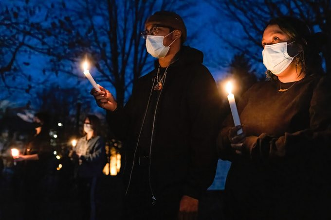 Khaila Carr, 24, of Columbus, Ohio holds a lit candle with her partner, Tyler, at a vigil for the eight people killed March 16, 2021 in a shooting in Atlanta, Georgia.