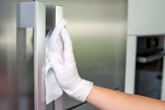 Woman Cleans refrigerator Handle Using Disinfectant Wipe, Coronavirus concept, COVID-19