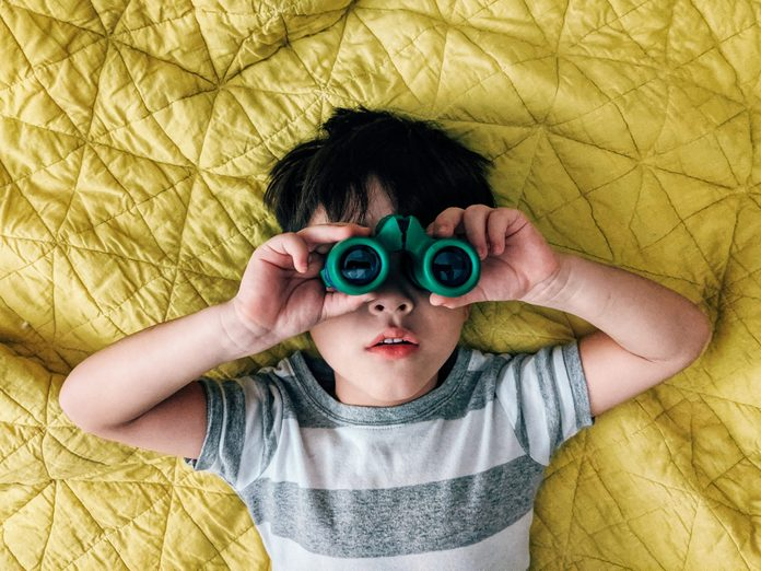 A child looks through binoculars while laying on a bed.