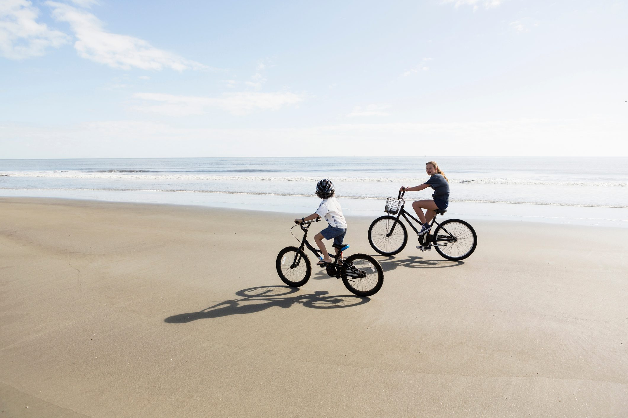 Siblings, a boy and girl cycling on a beach.