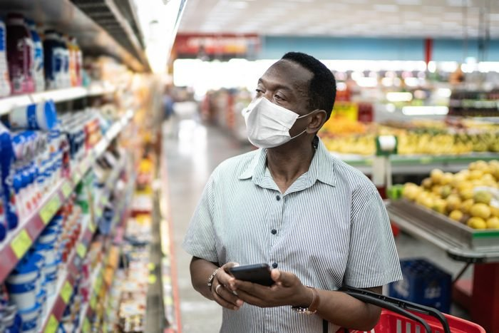 Mature man using mobile and choosing products in supermarket - using face mask