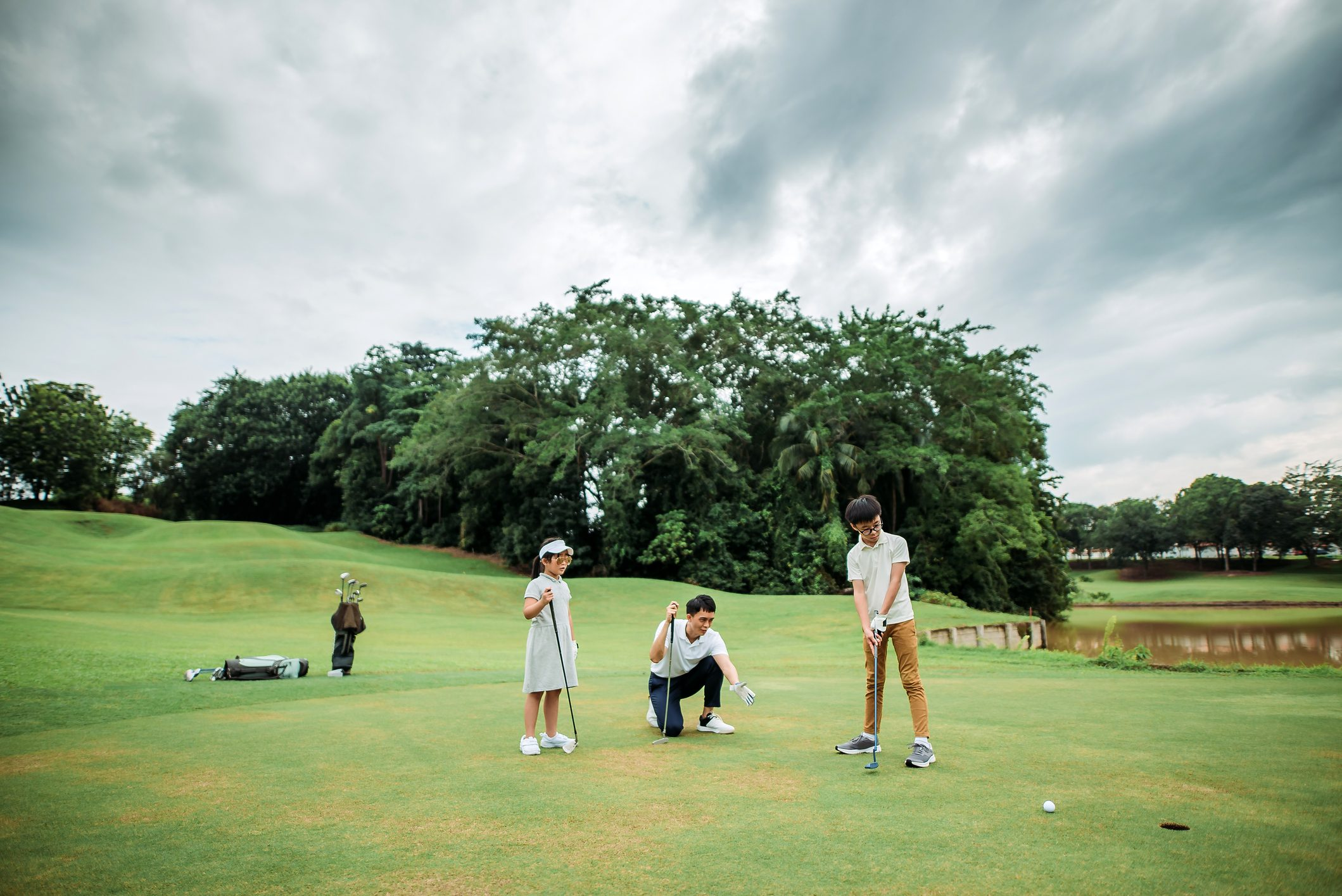 father golfing with son and daughter on father's day
