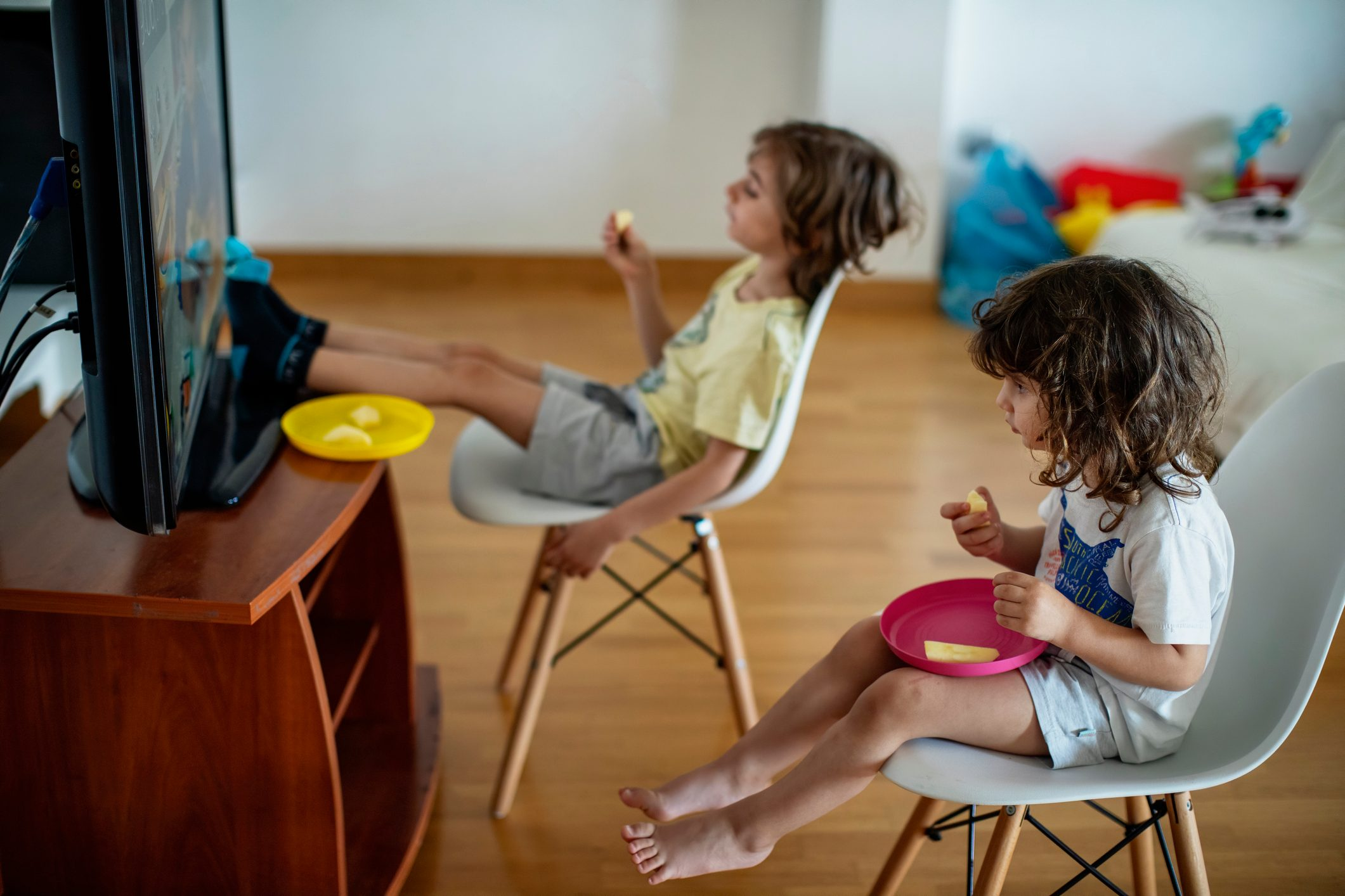 Kids eating in front of a television