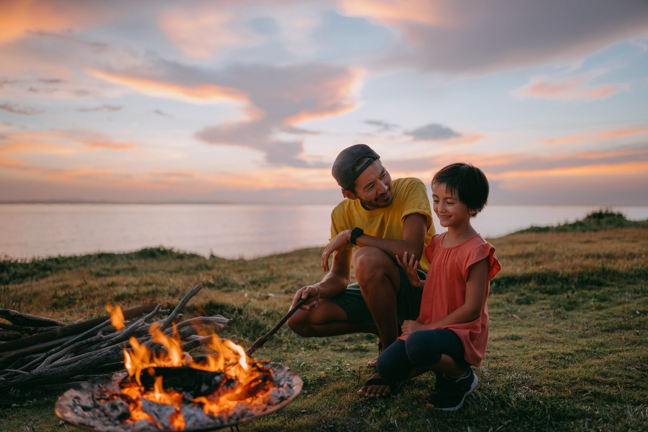 Father and daughter enjoying campfire at seaside campsite at sunset