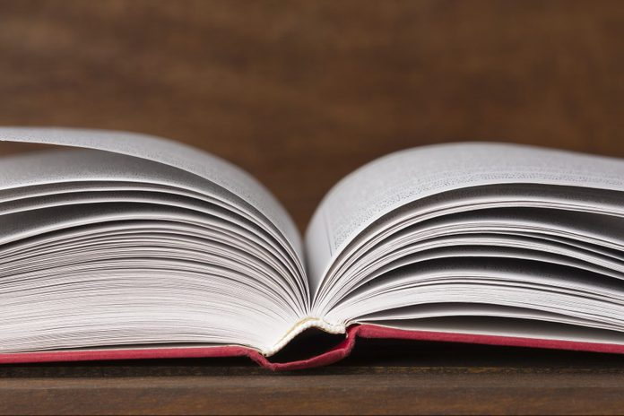 Close up of open book on old wooden background
