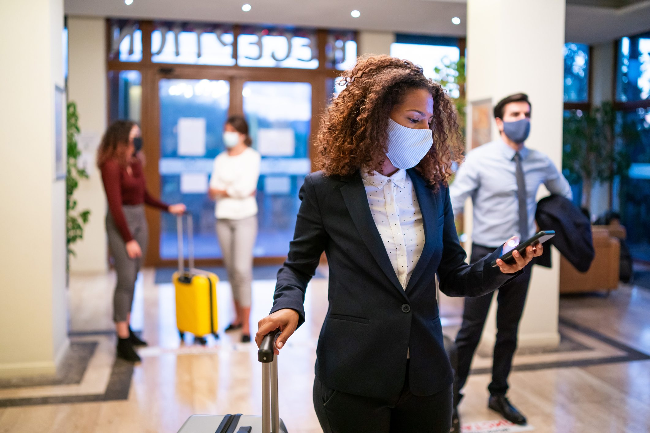 Hotel guests wearing face masks in the lobby; one woman is checking in on her smartphone