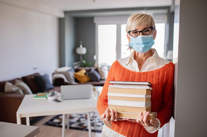 Portrait of professor with face mask at home, holding books