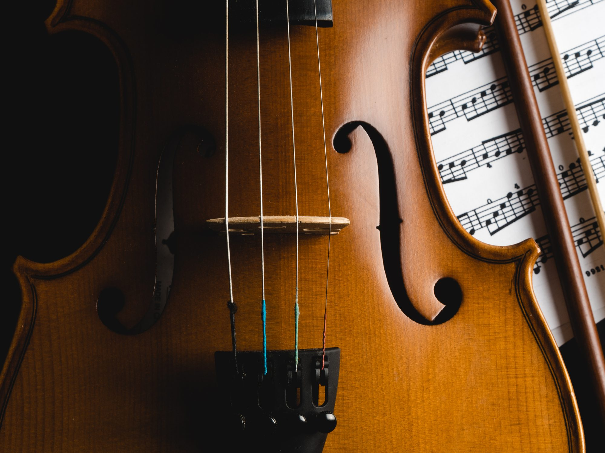 Cropped Image Of Violin against Black Background with sheet music and bow