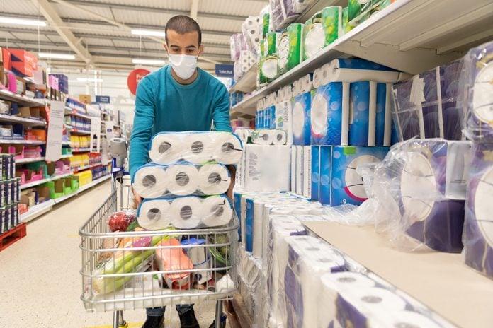 Man buying toilet paper at supermarket and wearing a face mask during coronavirus pandemic