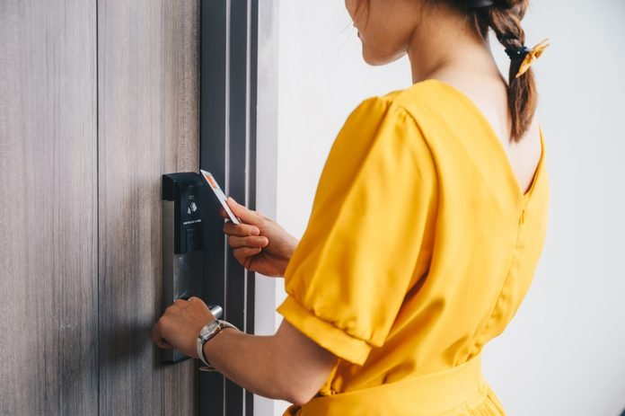 Cropped shot view of tourist woman using keycard to unlock an electronic door in luxury hotel.