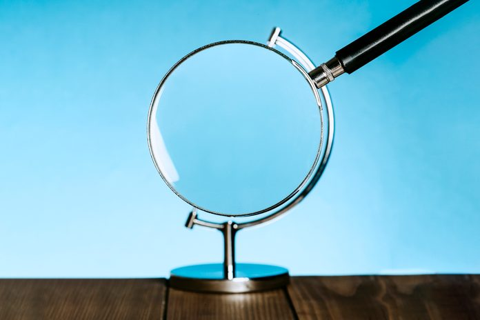 magnifying glass becomes the globe on a stand that usually holds a model of the earth