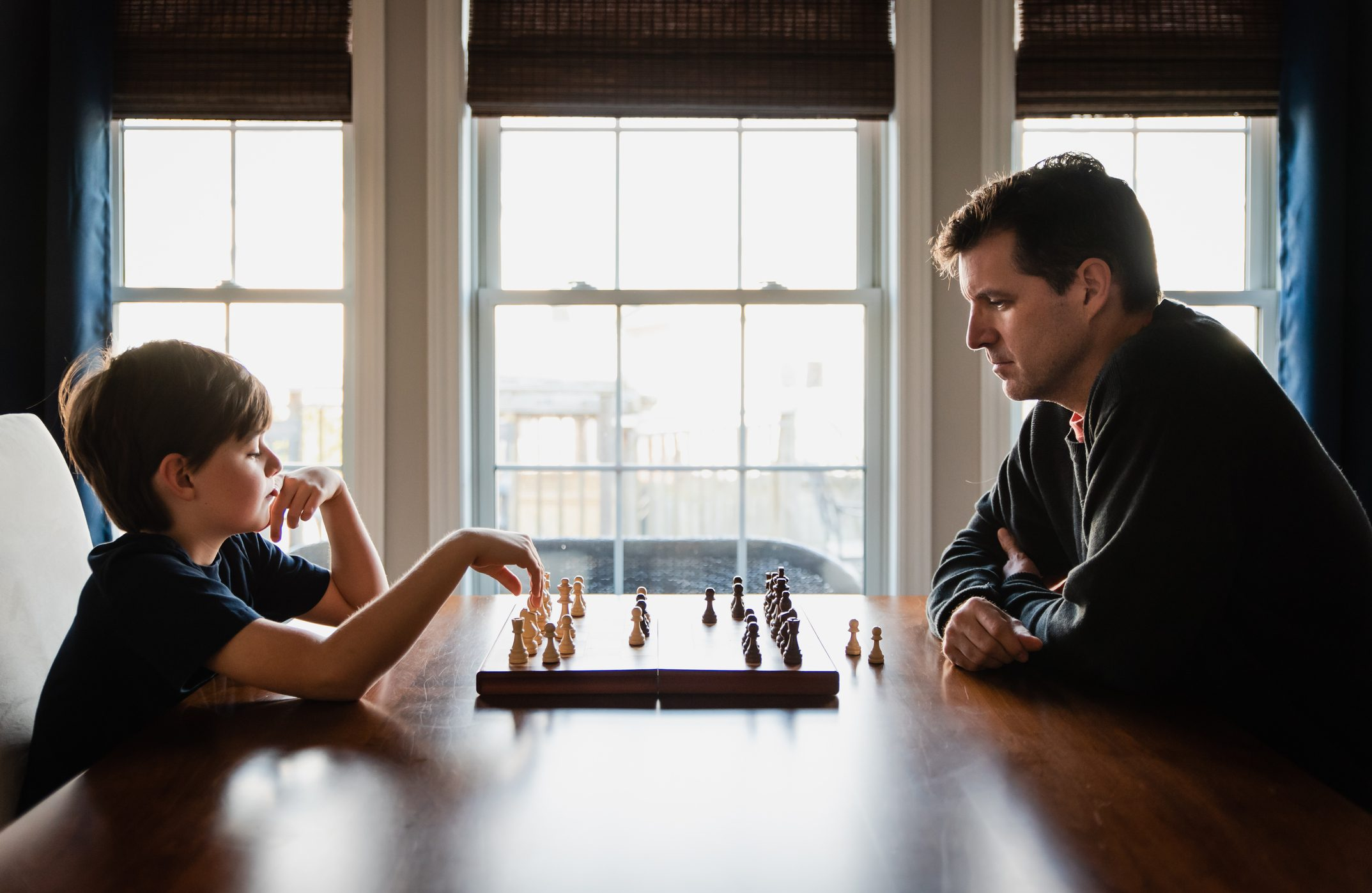 Father and son sitting at a table indoors playing a game of chess.