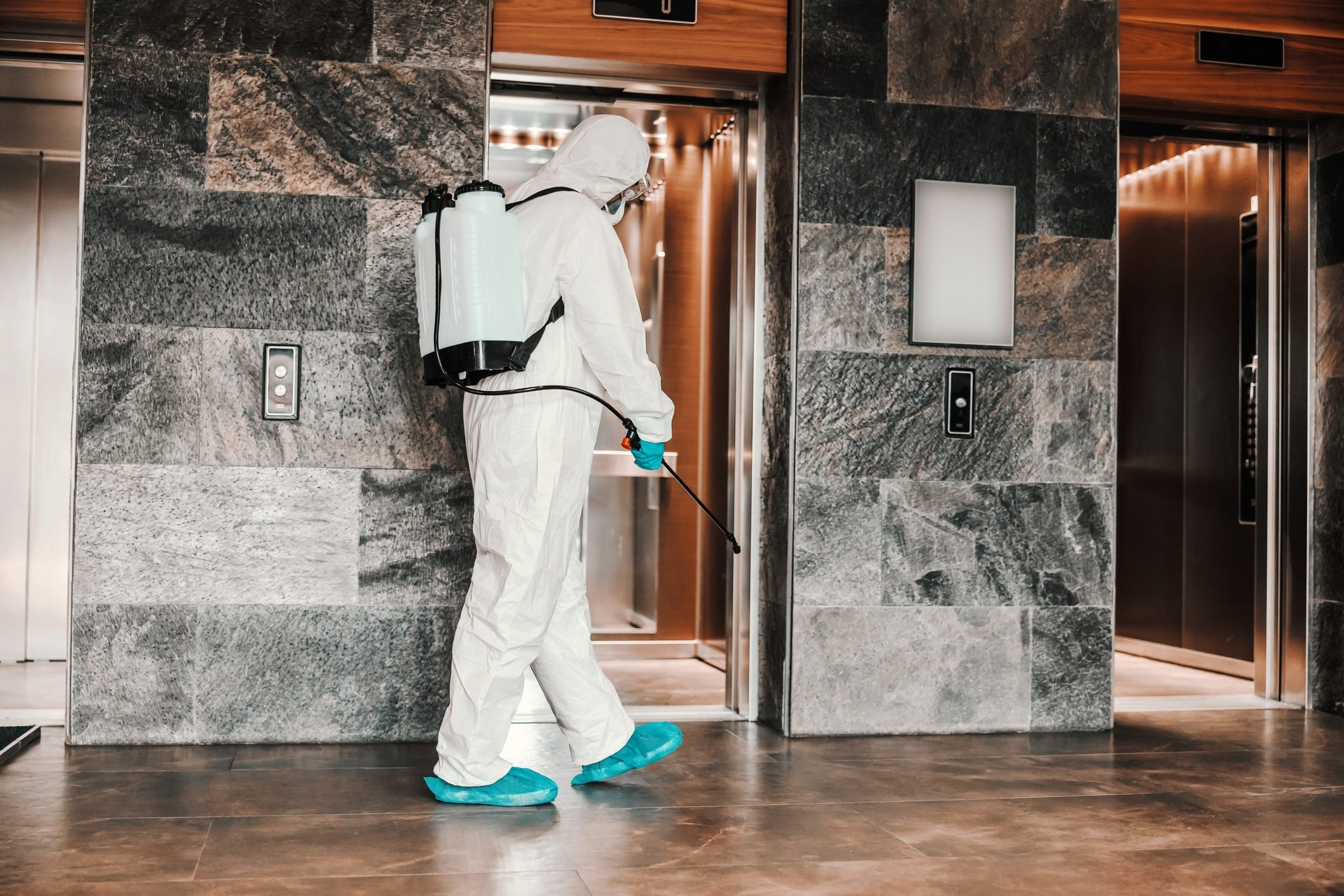 person spraying disinfectant around the elevator in the lobby of a hotel