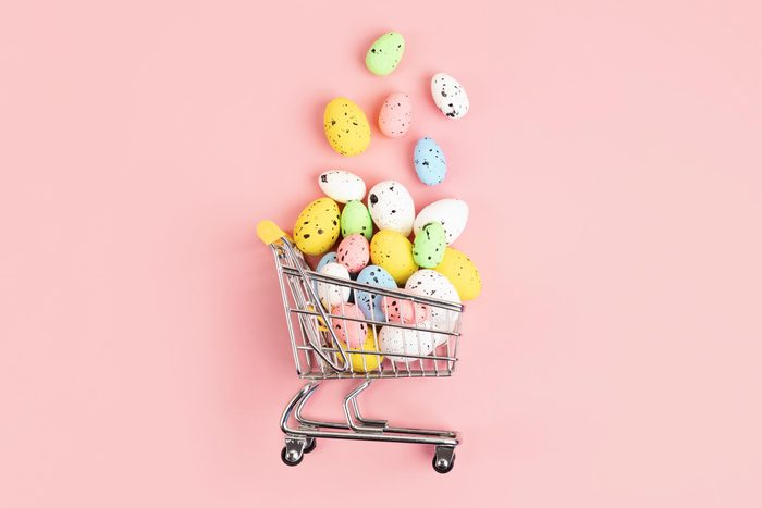toy grocery cart on it's side on pink background with candy easter eggs pouring out of the basket