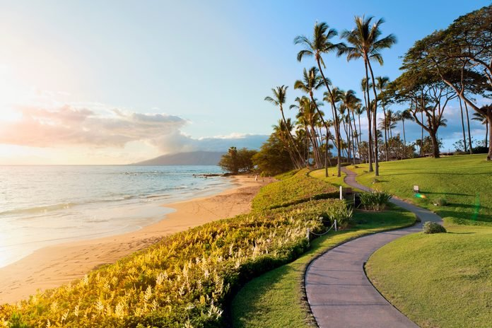 Tropical beach path with palm trees at sunset in the luxury resort destination of Wailea, Maui, Hawaii, USA.