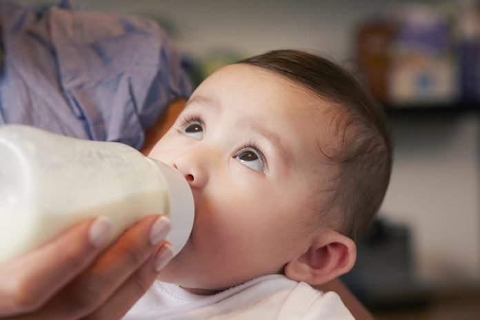 Baby girl drinking bottle of milk