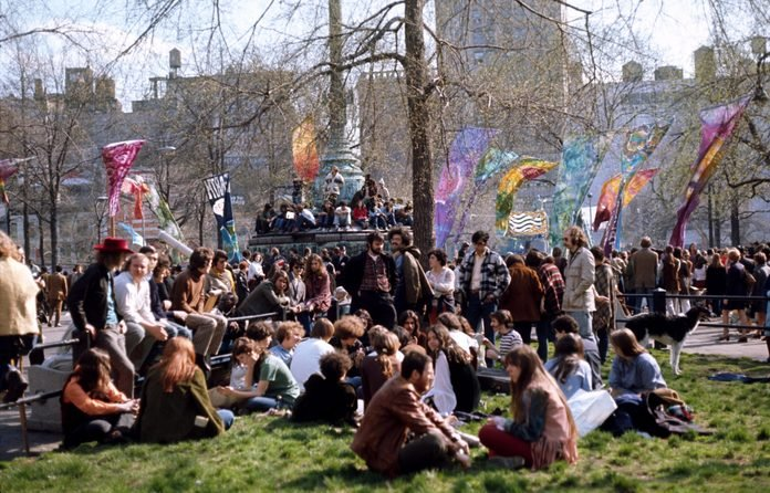 people gather in a park in New York City with banners to celebrate the first Earth Day, April 20, 1970