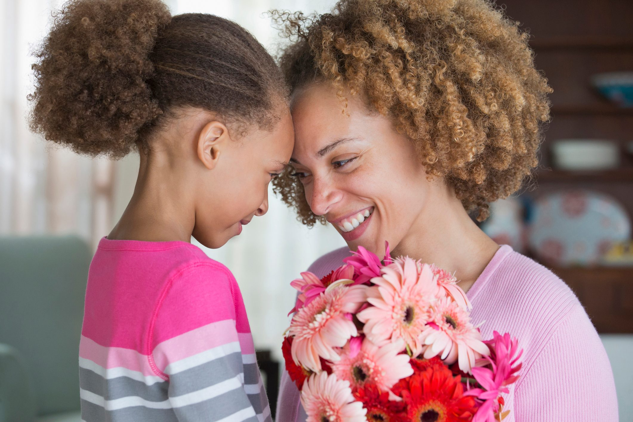 Black mother and daughter holding bouquet of flowers