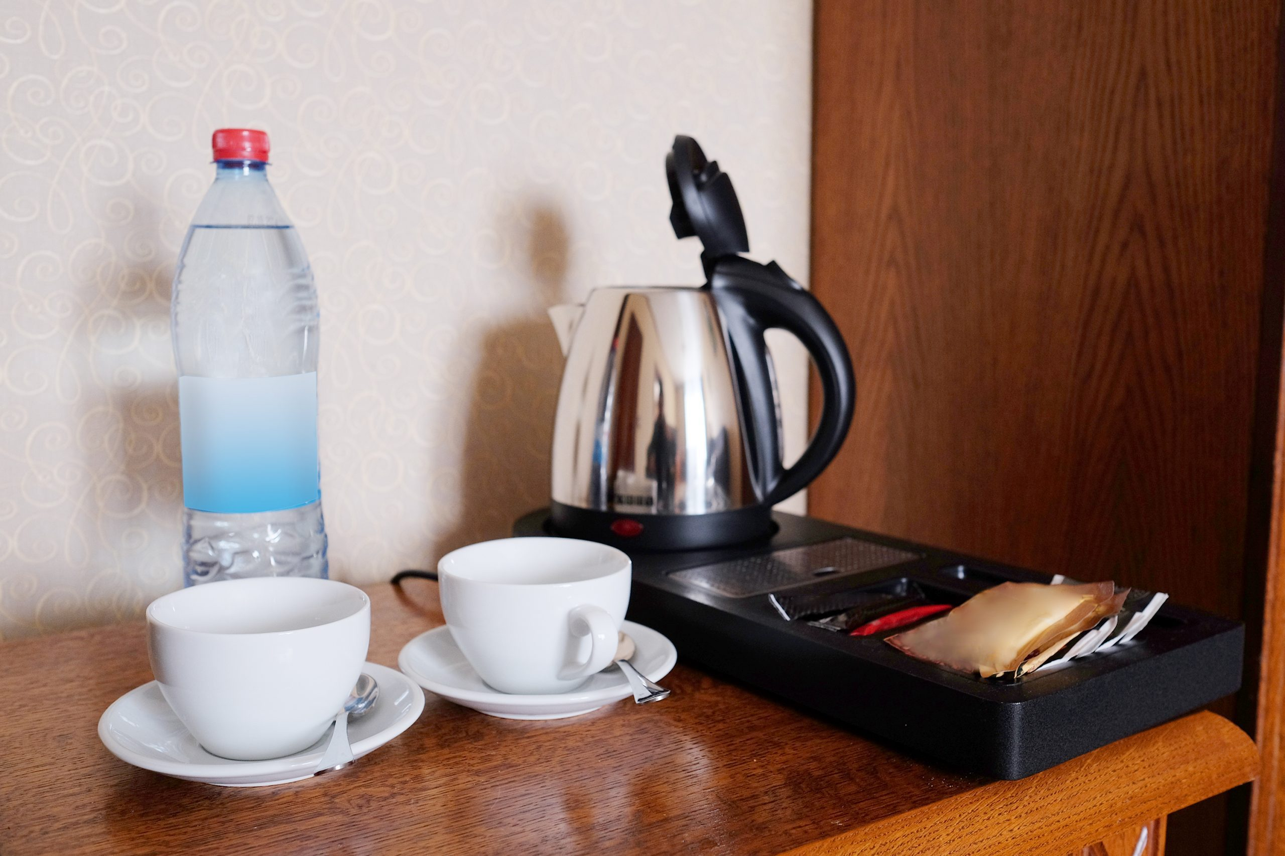 coffee maker in a hotel room next to mugs and a bottled water