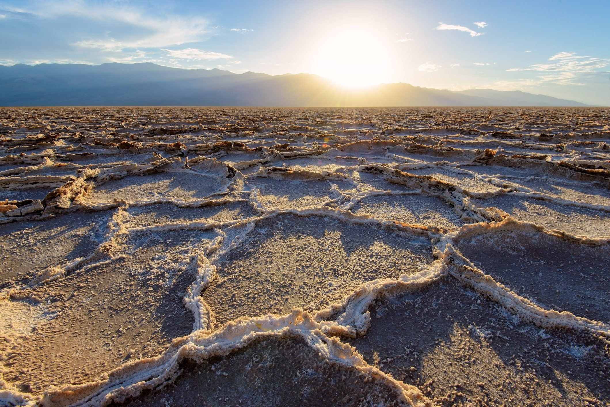sunset over patterns on the salt flats of Badwater Basin - Death Valley National Park in California