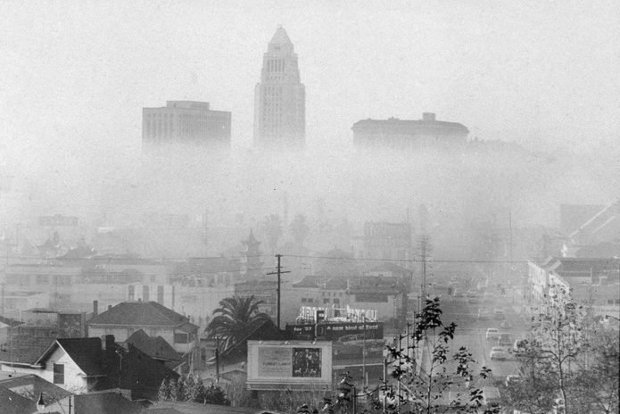 the skyline of downtown Los Angeles including the city hall (center) and the United States Courthouse (left), and Hall of Justice (right) shrouded and obscured by smog, a form of industrial and automotive air pollution particularly problematic in the area during the mid 20th Century, 1956.
