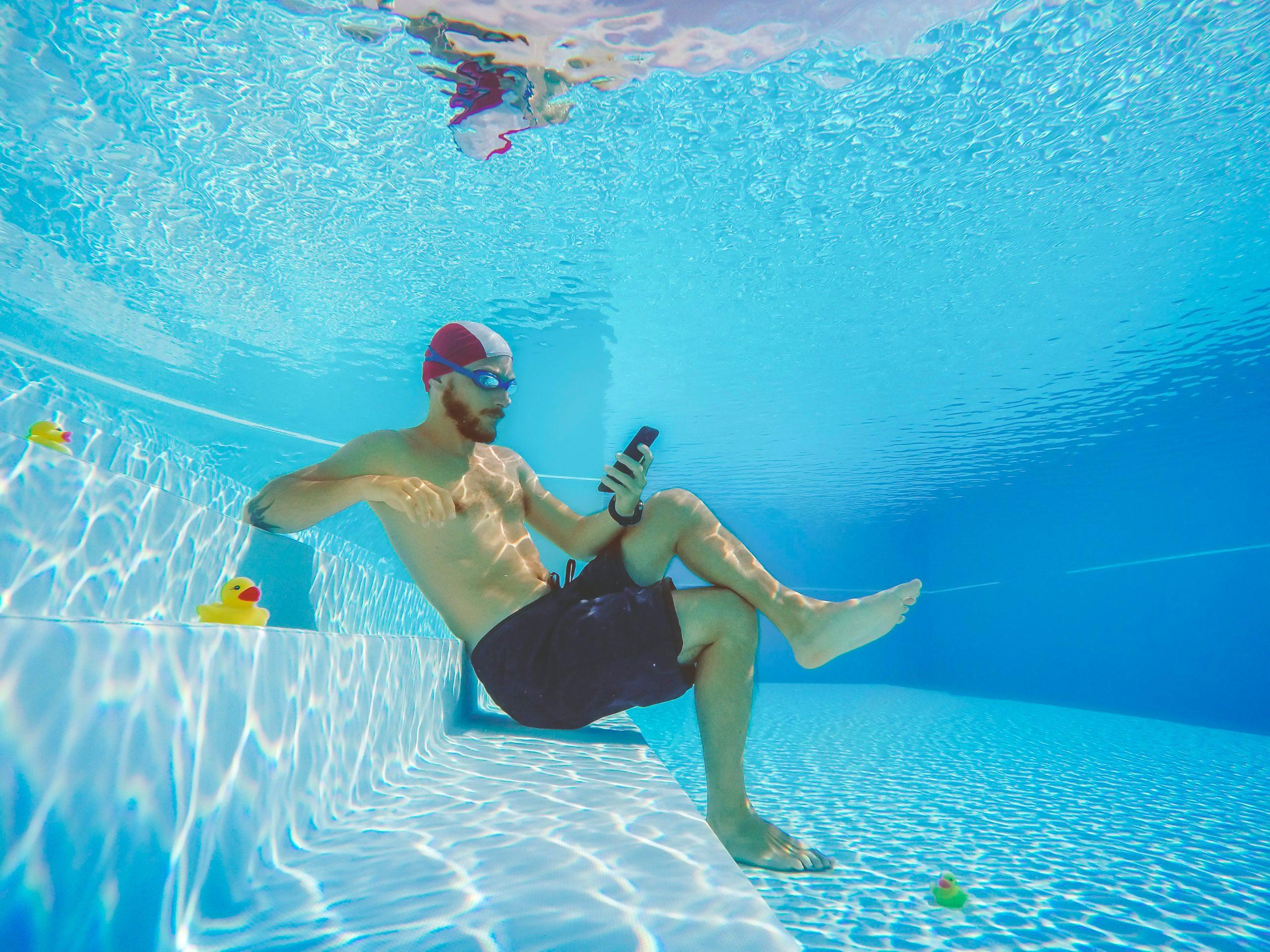man seated, using smartphone, underwater