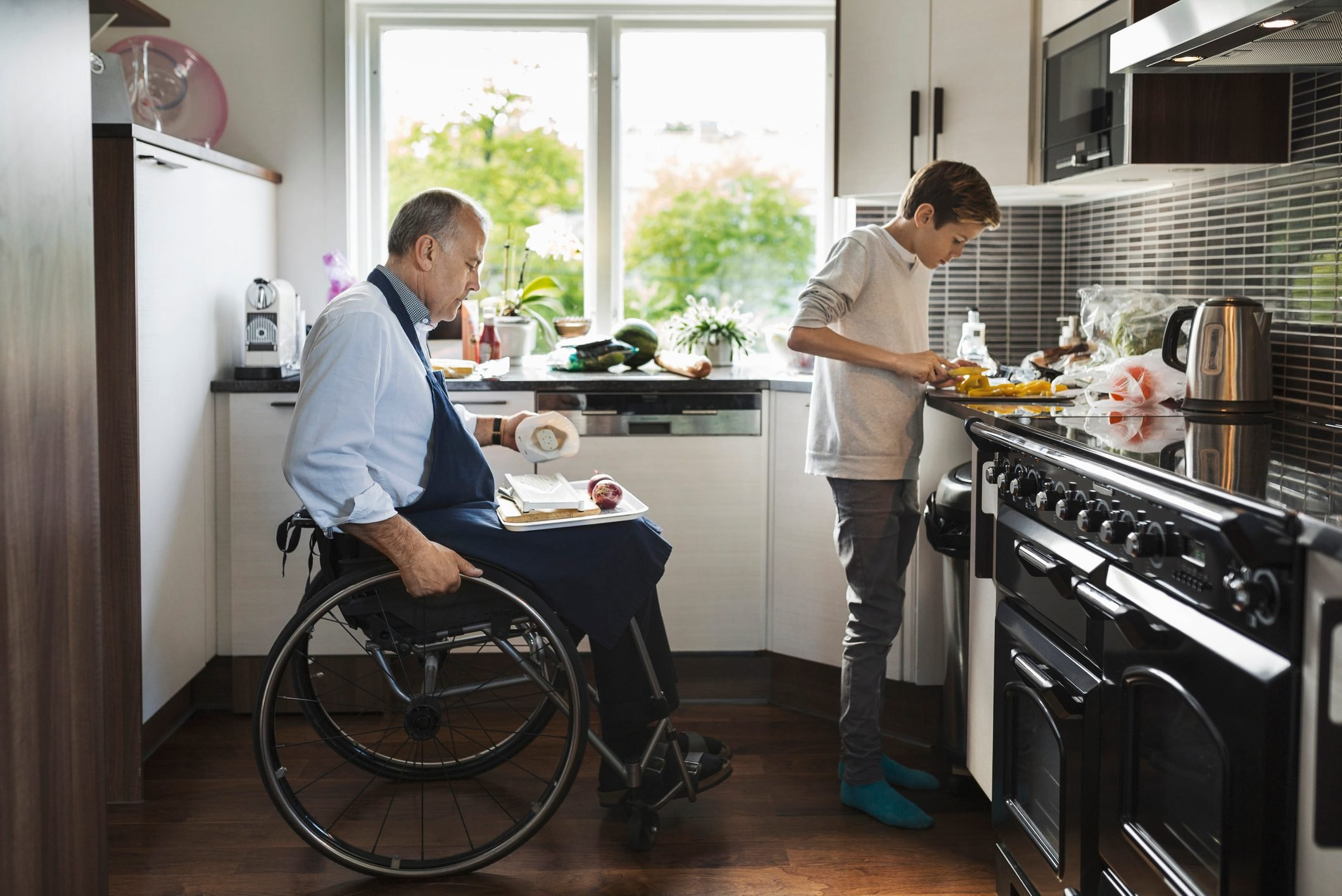 Son with disabled father cutting vegetables in kitchen