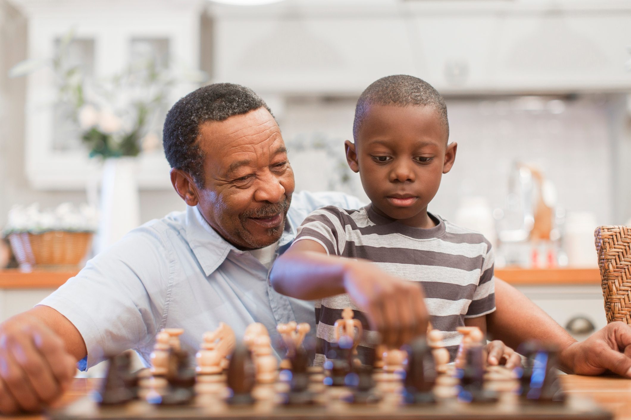 Senior man playing chess with his grandson (8-9), Cape Town, South Africa