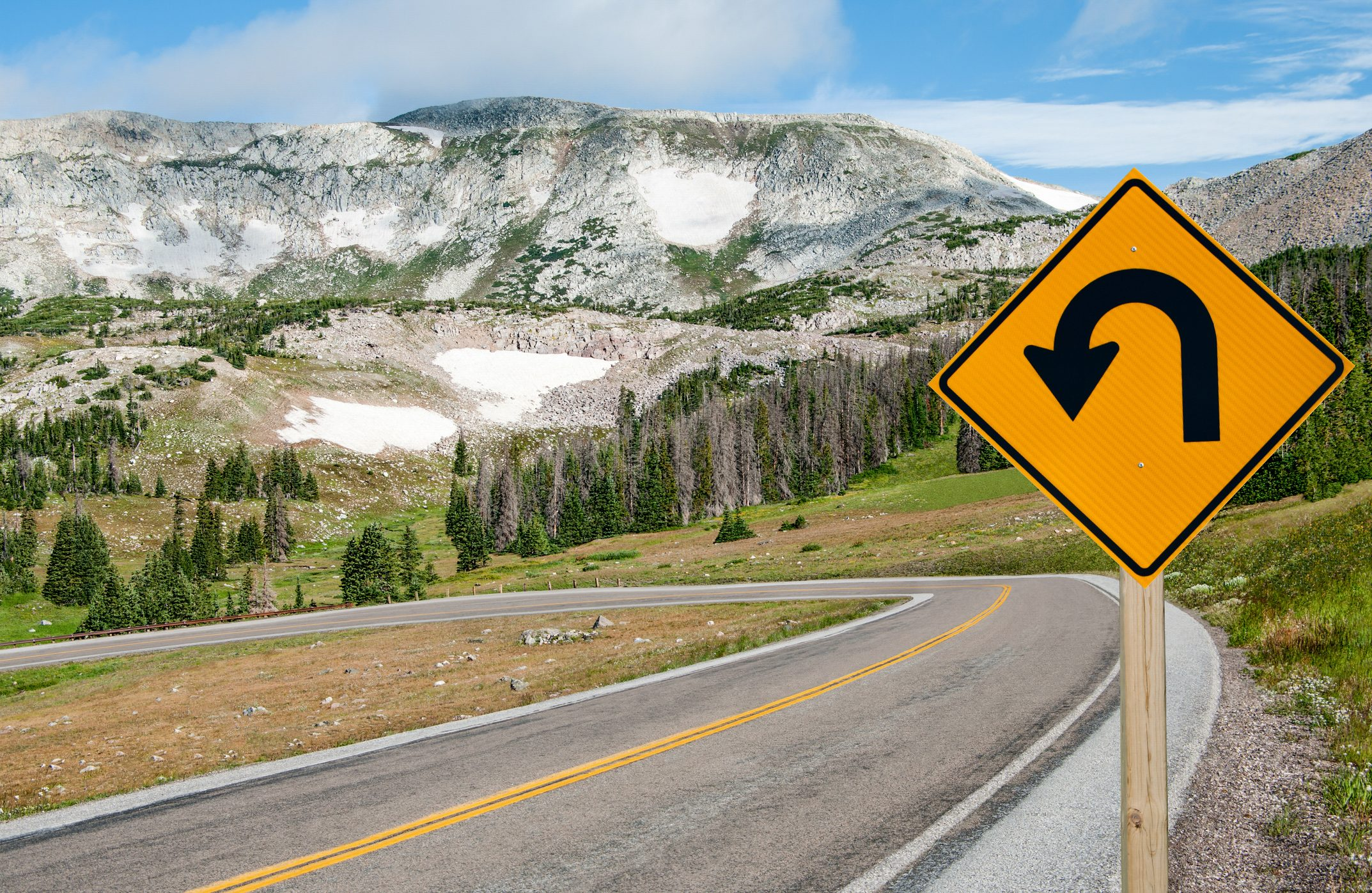 A sign warns motorists of a sharp bend ahead on the Snowy Range Scenic Byway in Wyoming.