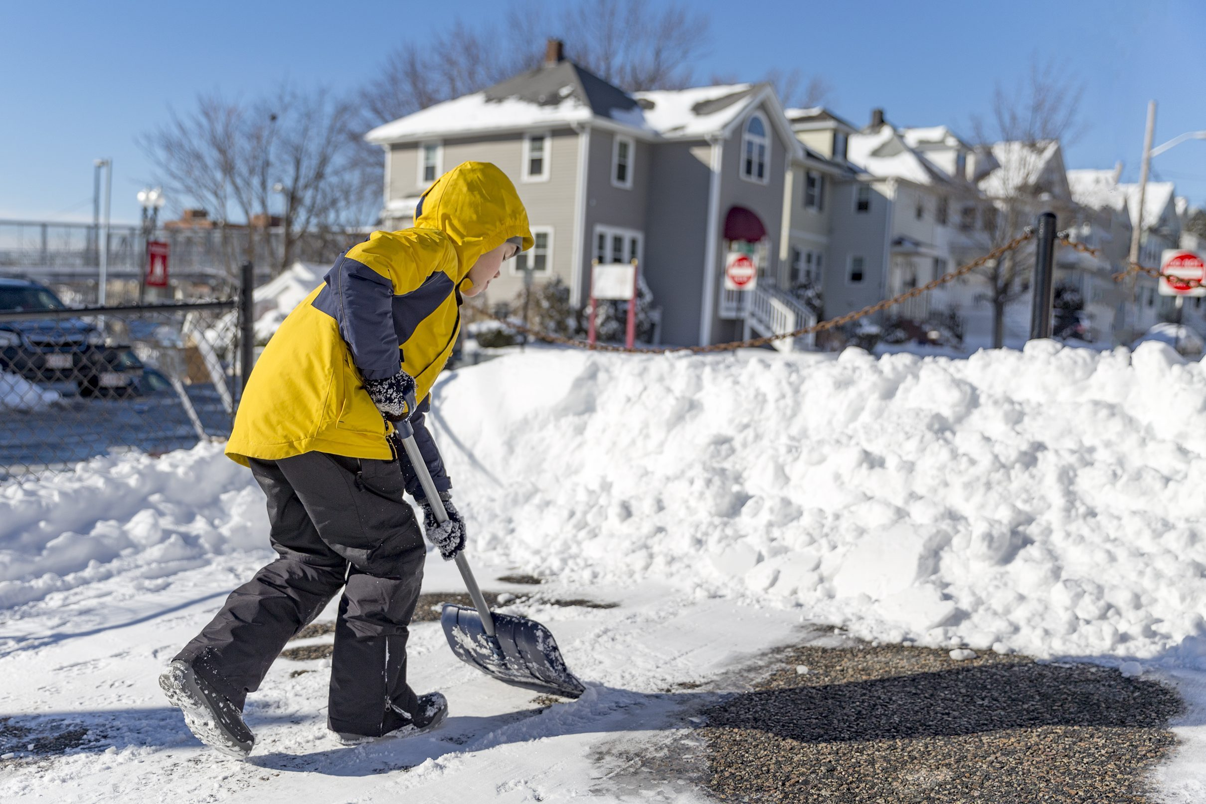 child cleans snow in the yard