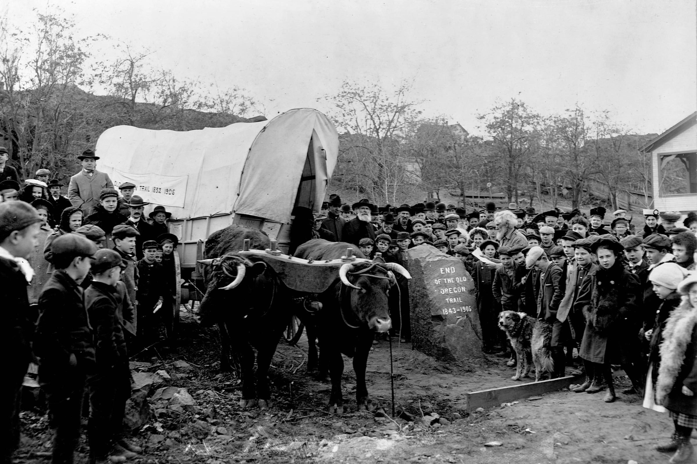 A crowd of the descendants of Oregon Trail settlers gathers together in The Dalles, Oregon, for a celebration at the inscribed stone that marks the trail's end. A covered wagon pulled by a team of oxen completes the occasion.