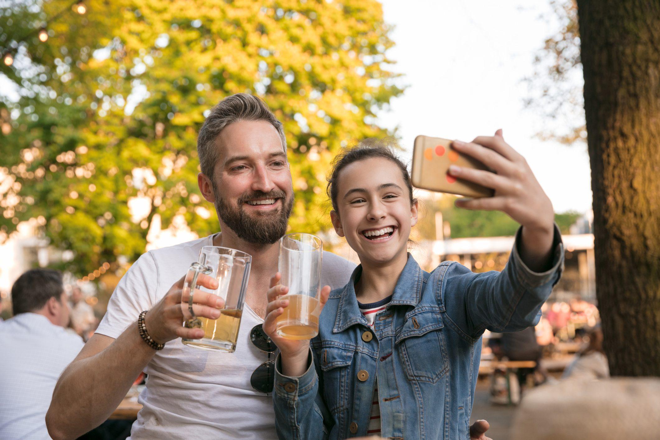 Happy daughter taking selfie while having drink at beer garden