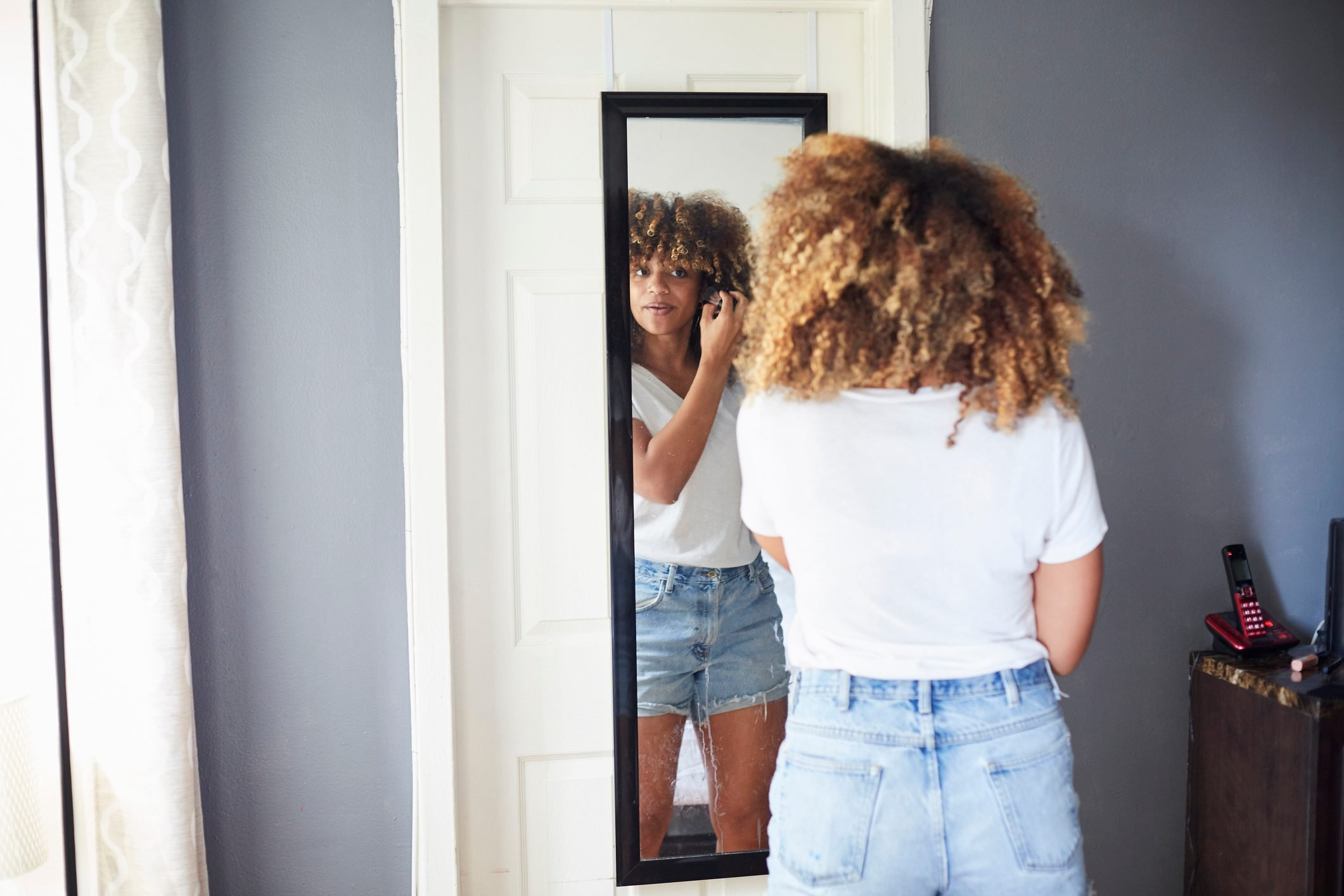 Black woman examining hair in mirror
