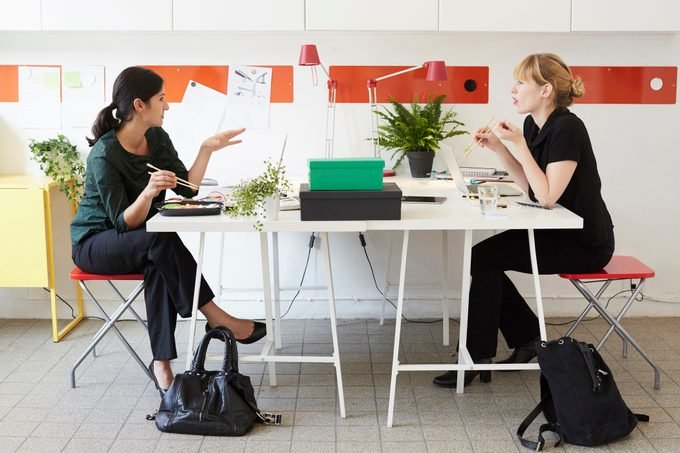 Full length of businesswomen talking while having lunch at table in office