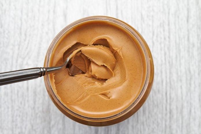 Peanut butter on spoon in jar