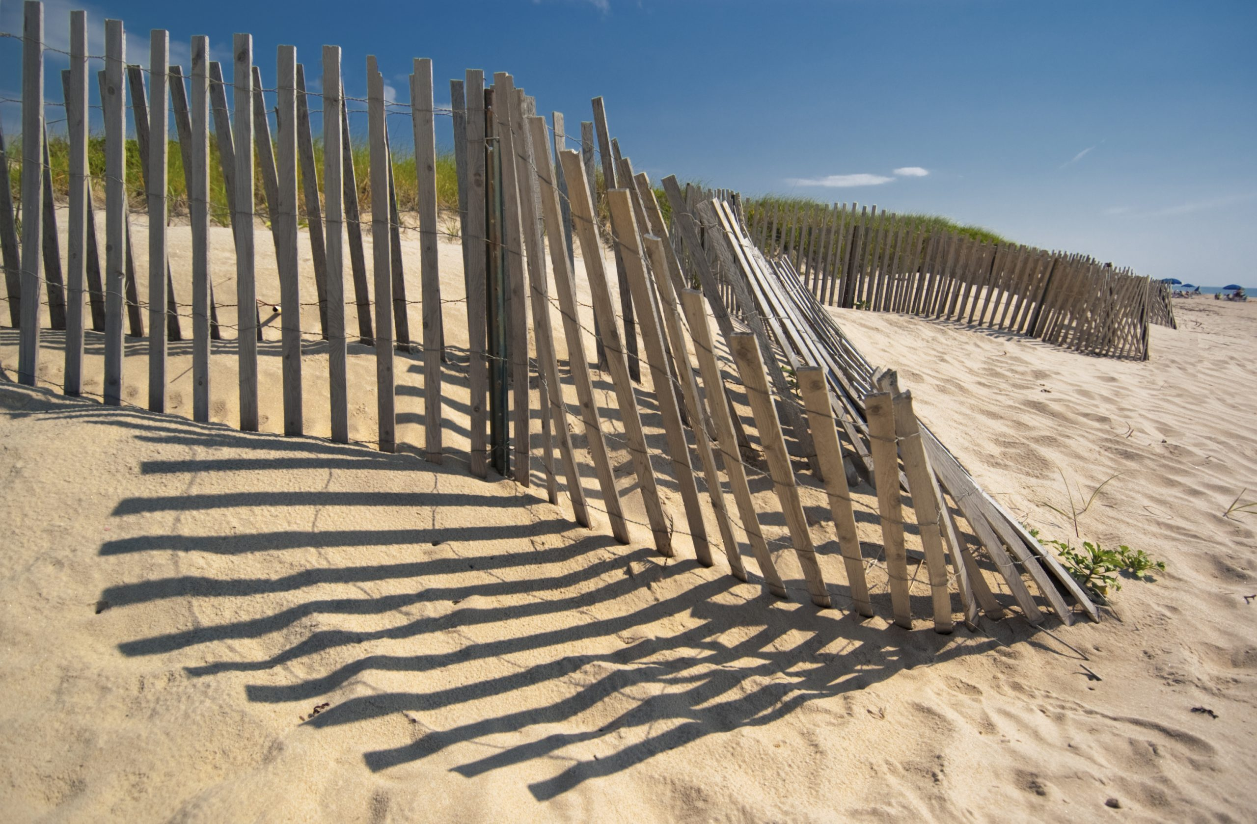 The low sun casts long shadows of a wooden fence on a sandy dune by the ocean at Amagansett beach, in the Hamptons, New York
