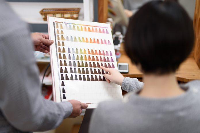 Female customer choosing hair color in hair salon