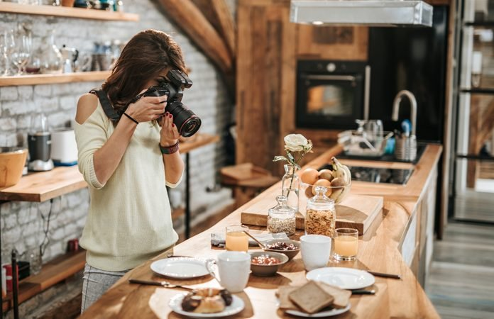 Female photographer taking photos of food at dining table.
