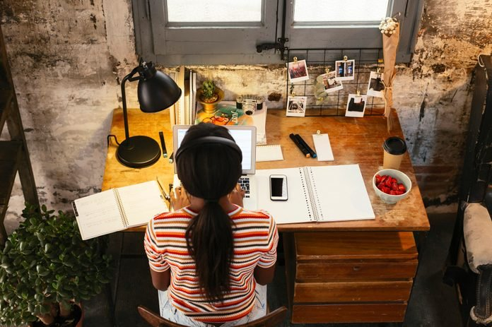 Back view of young woman sitting at desk in a loft working on laptop seen from above