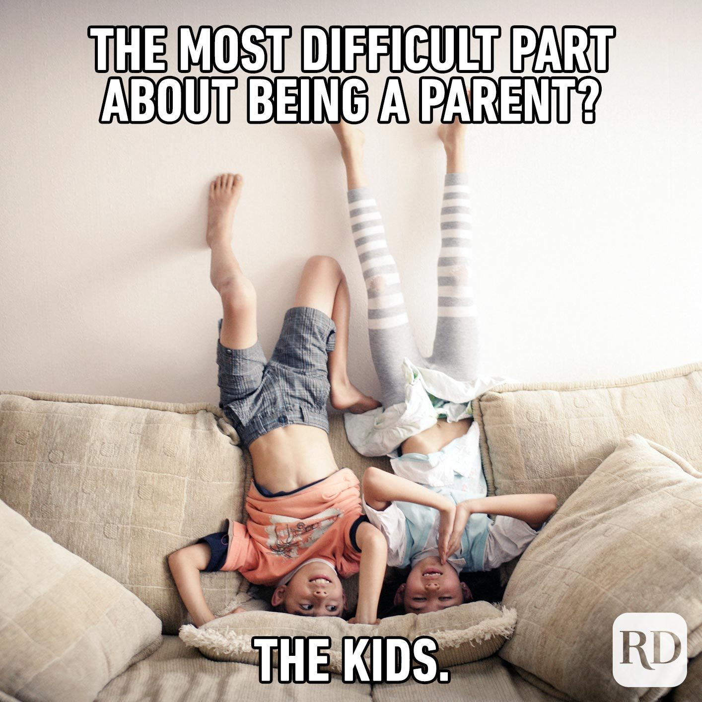 Two kids standing on their heads on a couch. MEME TEXT: The most difficult thing about being a parent? The kids