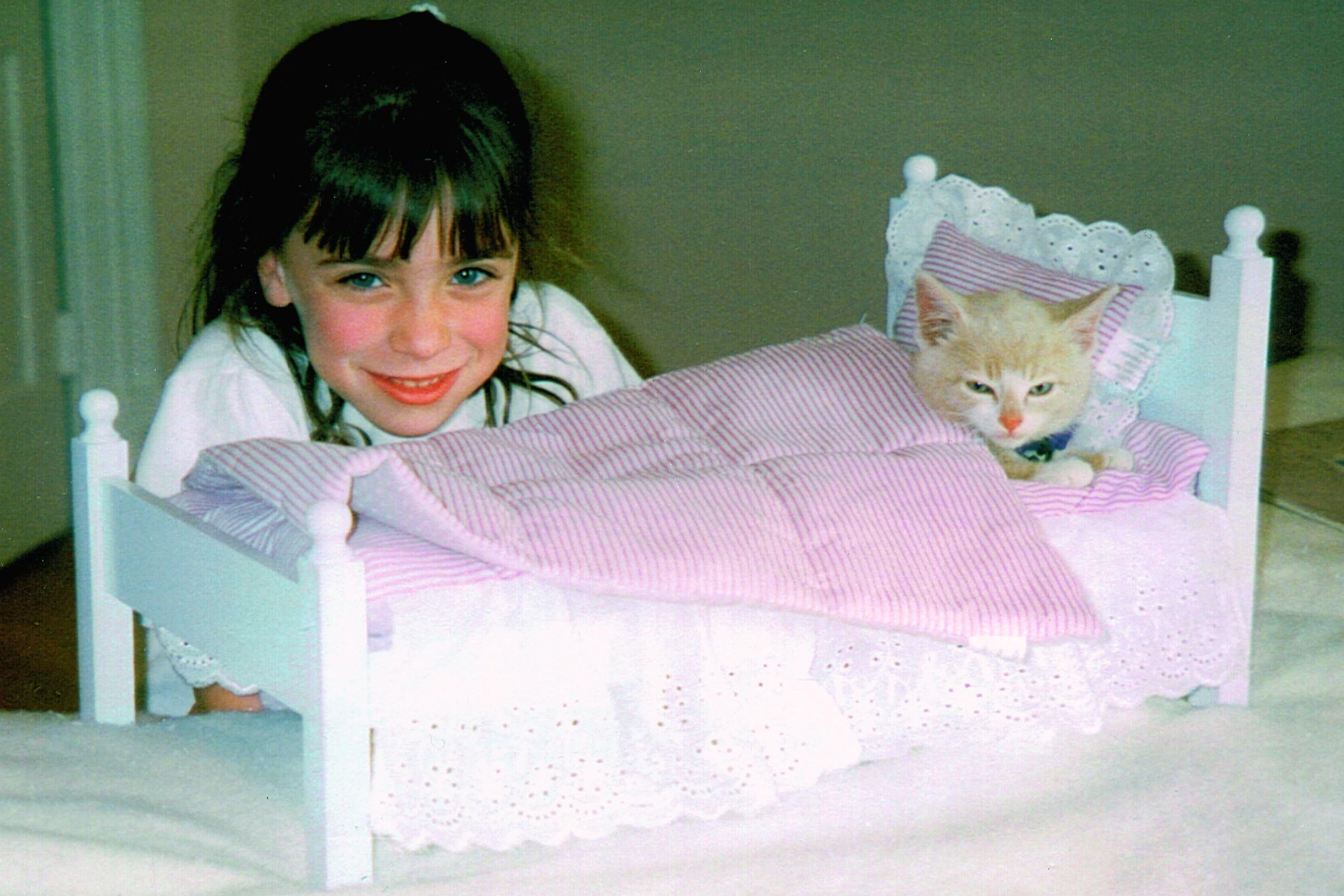 little girl with a kitten in a doll bed