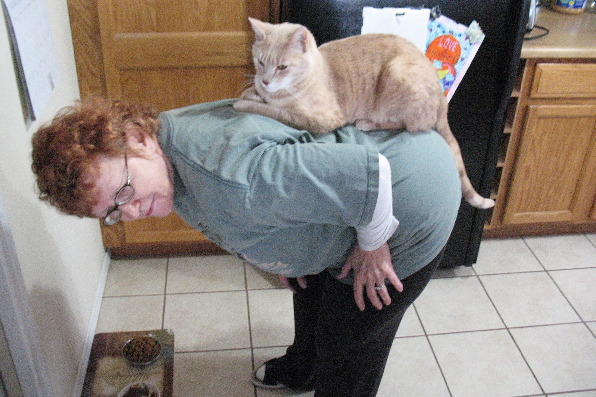 a woman bent over in the kitchen with a cat seated on her back