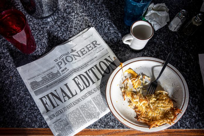 """a newspaper with large letters """"Final Edition"""" on the counter of a diner"""