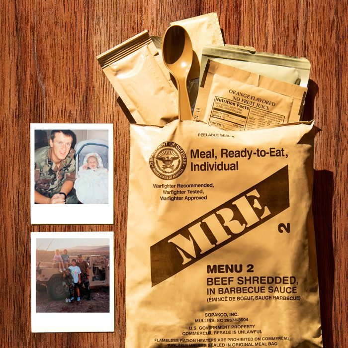 MRE package with contents spilling out the top with two personal polaroids; on wood background
