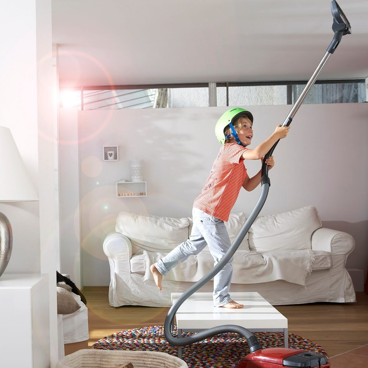 Boy In Living Room Hoovering The Ceiling
